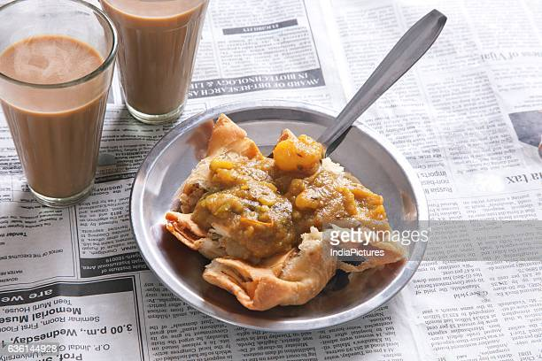 High Angle View Of Samosas And Tea On Newspaper