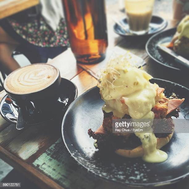 High Angle View Of Sandwich With Cappuccino Served On Table