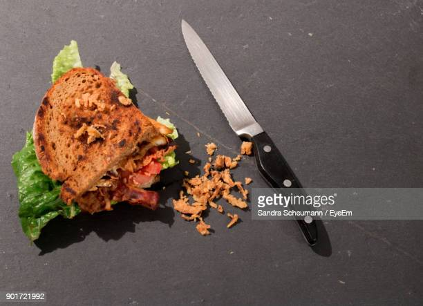 High Angle View Of Sandwich With Kitchen Knife On Table