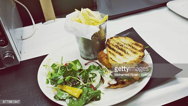 High Angle View Of Sandwich With Salad And French Fries Served In Plate