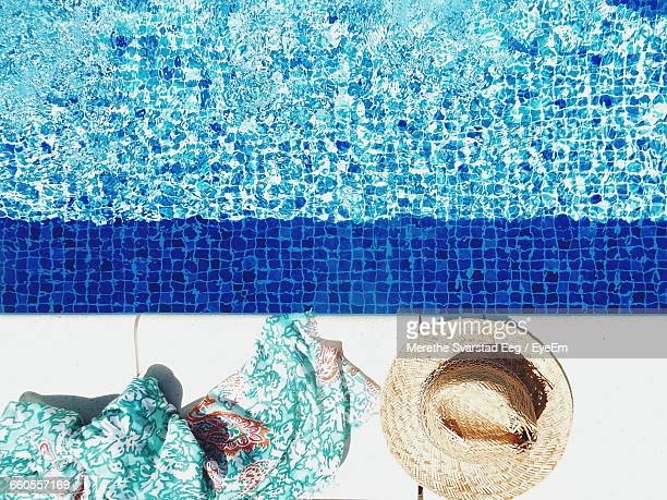 High Angle View Of Sarong And Straw Hat By Swimming Pool