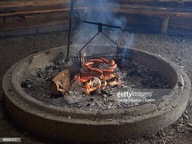 high angle view of sausages on barbecue grill in fire pit - teemu tretjakov stock pictures, royalty-free photos & images