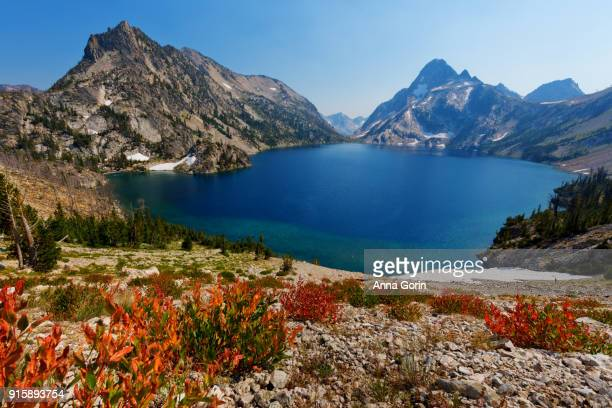 High angle view of Sawtooth Lake in summer with red plants in foreground, Stanley, Idaho