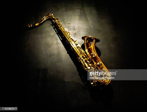 high angle view of saxophone on black background - saxophone stock pictures, royalty-free photos & images
