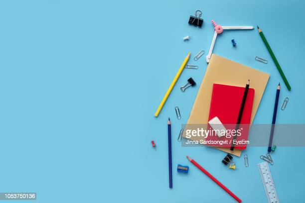 high angle view of school supplies over blue background - color pencil stock pictures, royalty-free photos & images