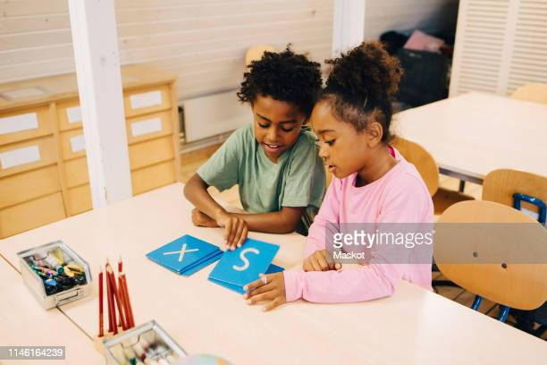high angle view of schoolboys learning alphabets on flash cards at table in classroom - children only stock pictures, royalty-free photos & images