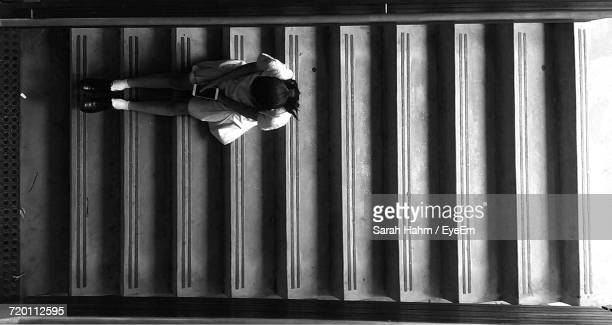 High Angle View Of Schoolgirl With Mobile Phone Sitting On Staircase