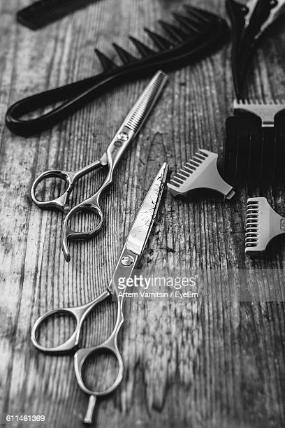 High Angle View Of Scissors And Comb On Table At Barber Shop