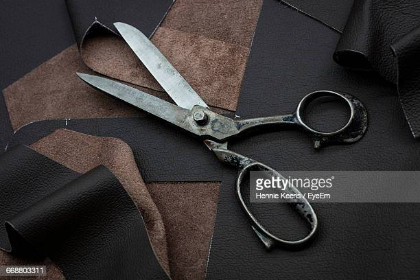 High Angle View Of Scissors On Leather Fabrics At Workshop