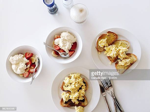 high angle view of scrambled eggs on toast and yogurt with fruits served on table - danielle reid stock pictures, royalty-free photos & images