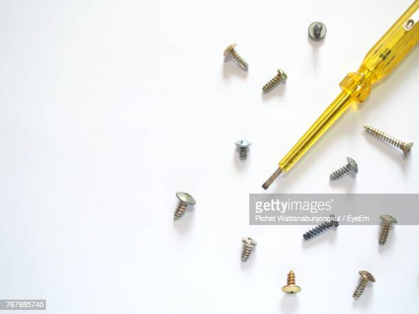 High Angle View Of Screw With Driver Over White Background