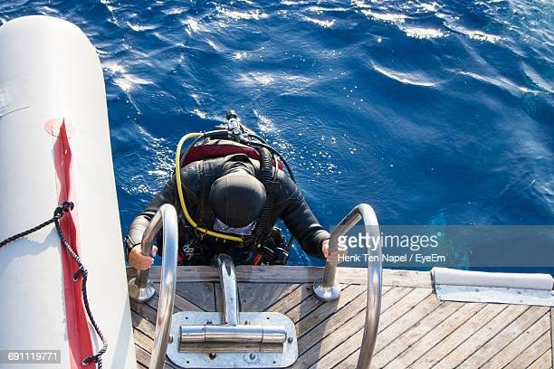 High Angle View Of Scuba Diver On Boat Ladder In Sea