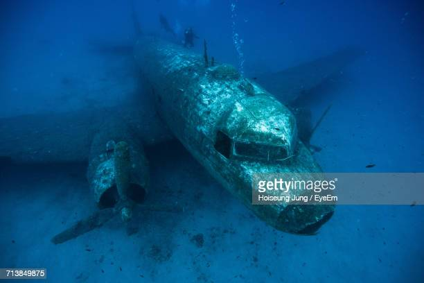 high angle view of scuba divers swimming over airplane wreck - airplane crash stock pictures, royalty-free photos & images