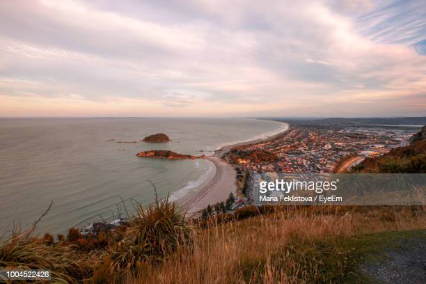 high angle view of sea against sky during sunset - mount maunganui stock pictures, royalty-free photos & images