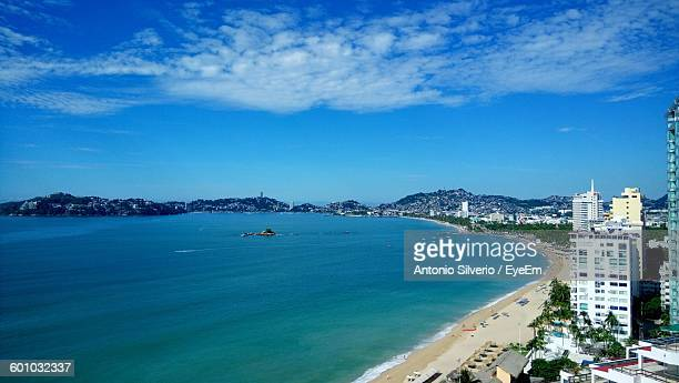 high angle view of sea and buildings against cloudy sky - アカプルコ ストックフォトと画像