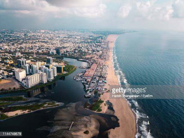 high angle view of sea and buildings against sky - chennai stock pictures, royalty-free photos & images