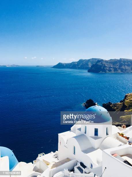 high angle view of sea and buildings against sky - greek islands stock pictures, royalty-free photos & images