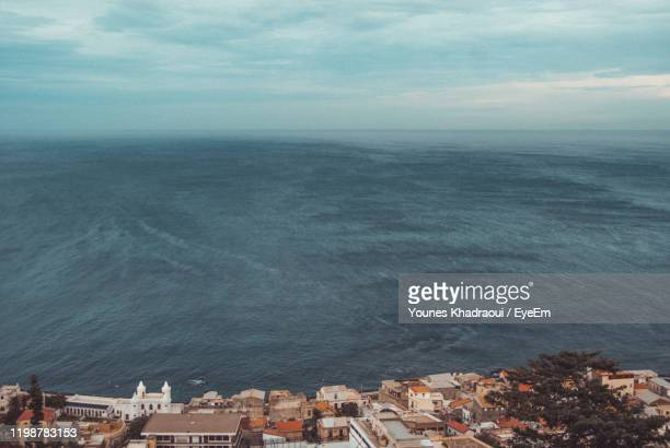 high angle view of sea and buildings against sky - アルジェー ストックフォトと画像