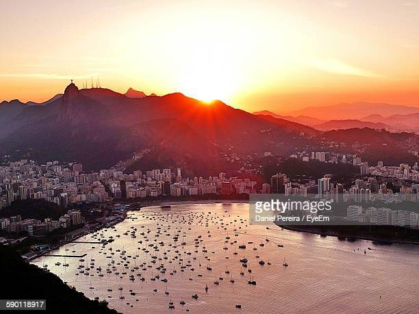 High Angle View Of Sea And Buildings At Sunset