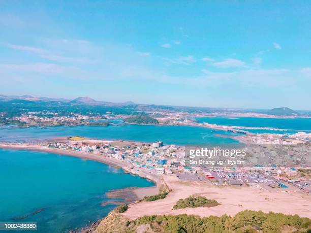high angle view of sea and city against sky - jeju stock photos and pictures