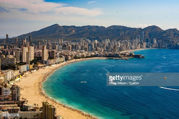 high angle view of sea and cityscape against sky - valencia spanje stockfoto's en -beelden