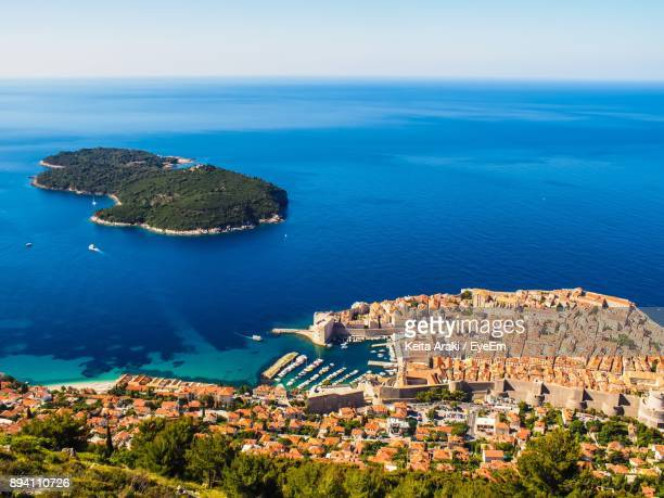 High Angle View Of Sea By Cityscape Against Sky