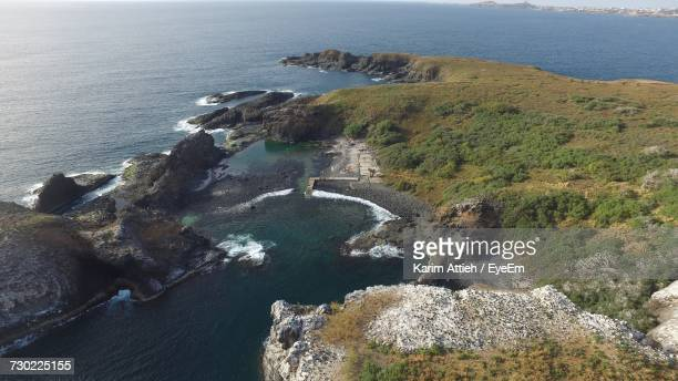 High Angle View Of Sea By Cliff Against Sky
