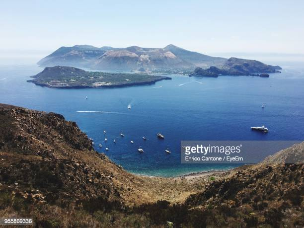 high angle view of sea by rock formations against sky - aeolian islands stock pictures, royalty-free photos & images