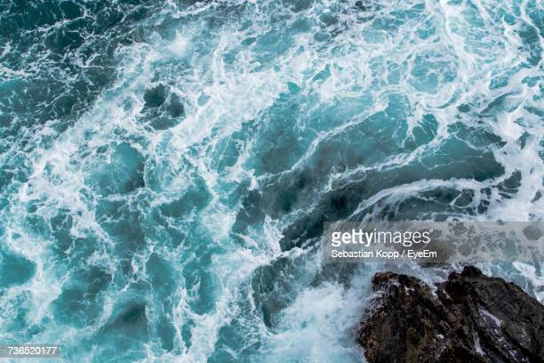 High Angle View Of Sea Splashing On Rock During High Tide