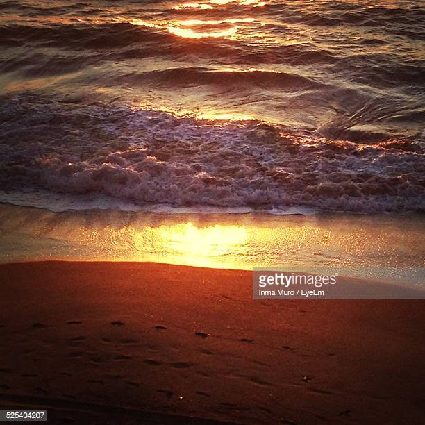 high angle view of sea surf by sand during sunset - muro stock photos and pictures