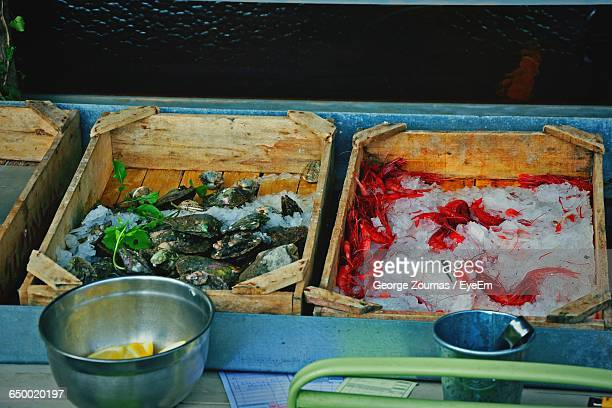 High Angle View Of Seafood In Wooden Crates For Sale At Market