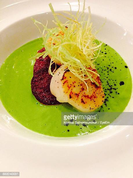 High Angle View Of Seared Scallop And Beetroot And Green Pea Sauce Served In Plate