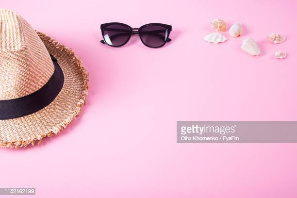 high angle view of seashells with sunglasses and sun hat on pink background - vêtement pour femmes photos et images de collection