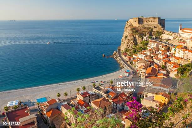 High angle view of seaside town with castle on cliff and sandy beach on the Mediterranean coast.