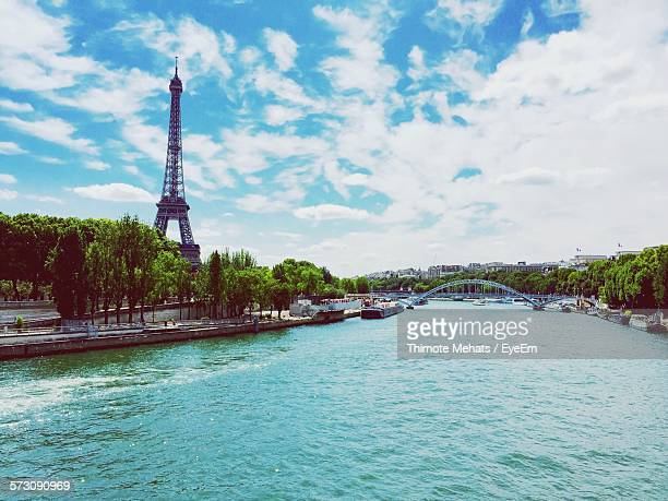 High Angle View Of Seine River By Eiffel Tower Against Cloudy Sky
