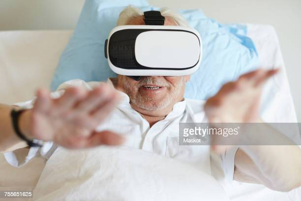 High angle view of senior man gesturing while using VR glasses on bed in hospital ward