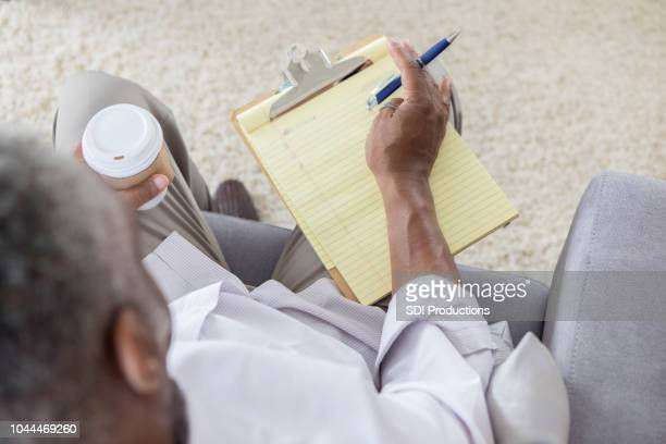 high angle view of senior man making to do list - to do list stock pictures, royalty-free photos & images
