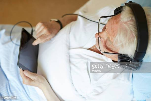 High angle view of senior man wearing headphones while touching digital tablet in hospital ward