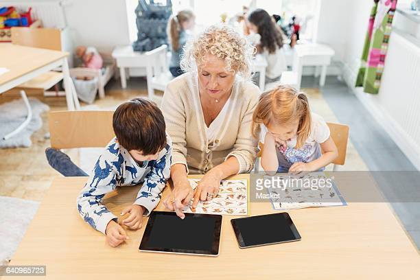 High angle view of senior teacher and children with animal charts and digital tablets