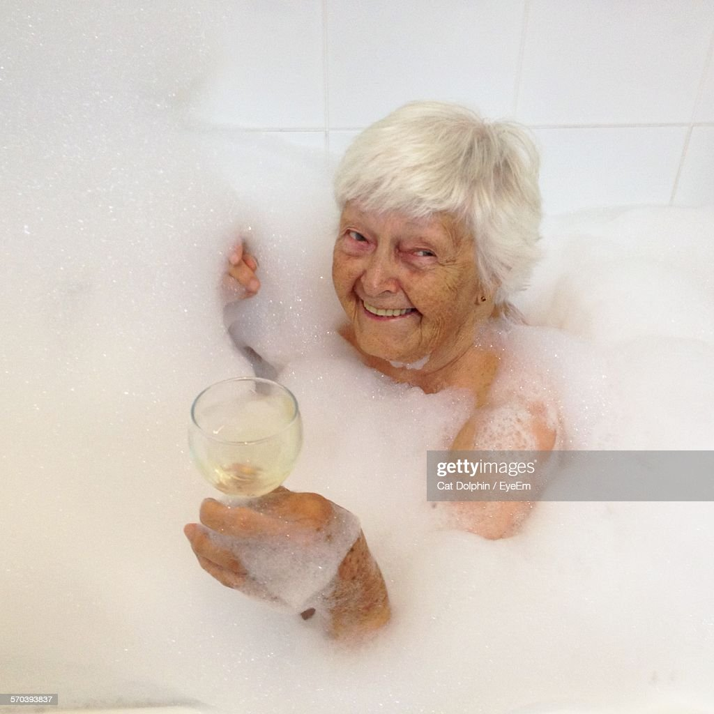 High Angle View Of Senior Woman In Bathtub With Bubbles Holding White Wine