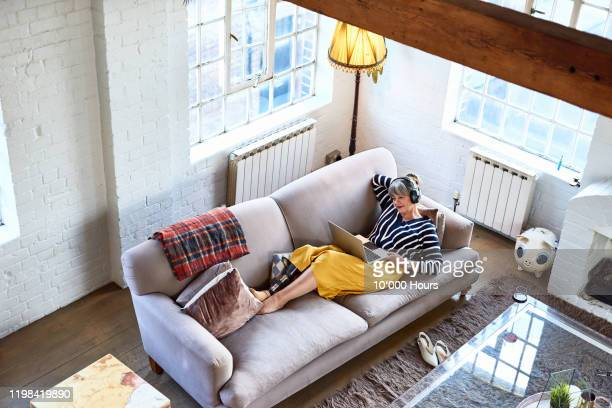 high angle view of senior woman on sofa with laptop - stream stock pictures, royalty-free photos & images