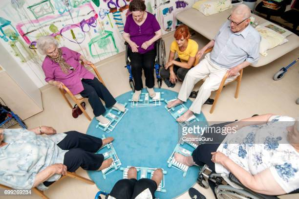 High Angle View Of Seniors Having Foot Massage Using Foot Roller