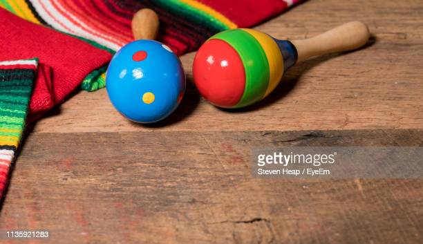 High Angle View Of Serape And Maracas On Wooden Table