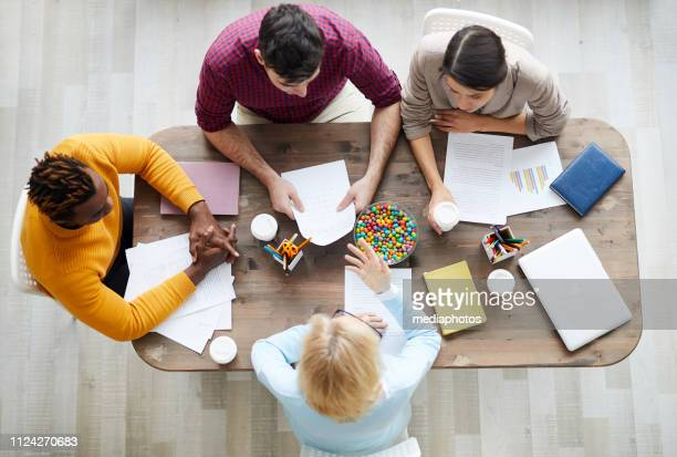 High angle view of serious business specialists sitting at table and discussing ideas and strategies at meeting: blond-haired lady gesturing hand while explaining her idea