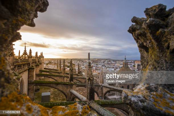high angle view of seville cathedral against cityscape during sunset - capital cities stock pictures, royalty-free photos & images