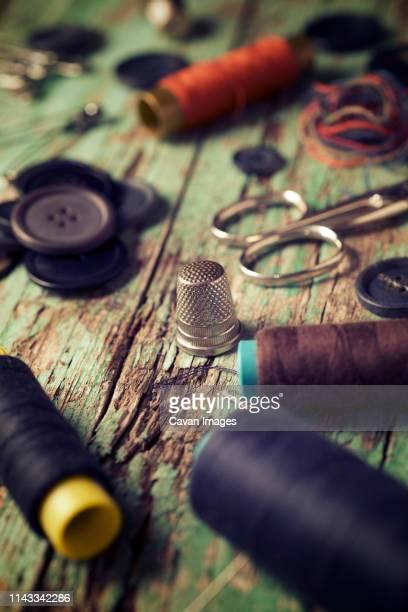 high angle view of sewing items on old wooden table - handwerkprodukten stockfoto's en -beelden