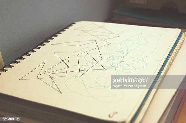 High Angle View Of Shapes Drawn In Spiral Notebook