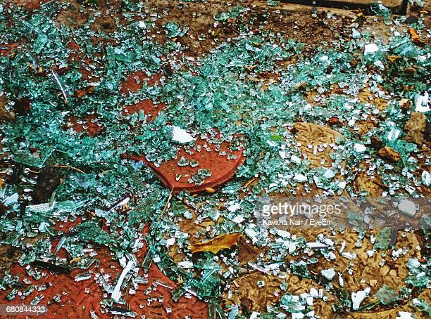 High Angle View Of Shattered Glass Pieces On Field