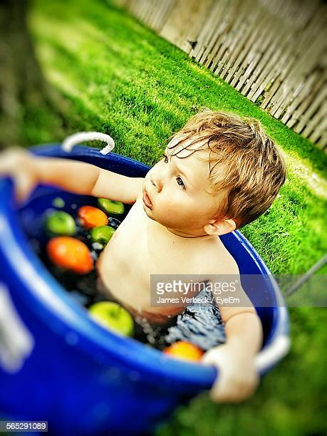 High Angle View Of Shirtless Boy In Bathtub On Grassy Field