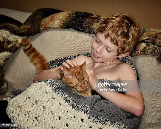 High Angle View Of Shirtless Boy Playing With Cat In Knitted Blanket